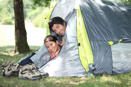 Young couple peeking out of their tent photo