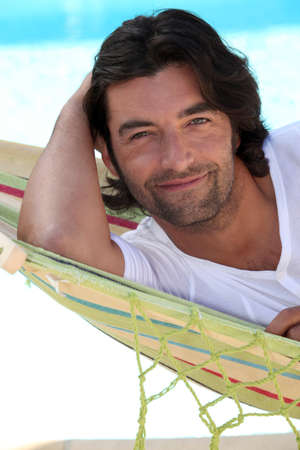 Man at beach laid in hammock Stock Photo - 12500086
