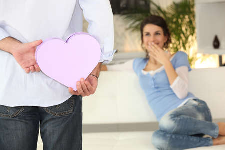Man surprising woman with gift photo