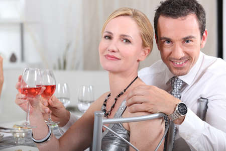 Couple with rose wine at a dinner party Stock Photo - 12500435
