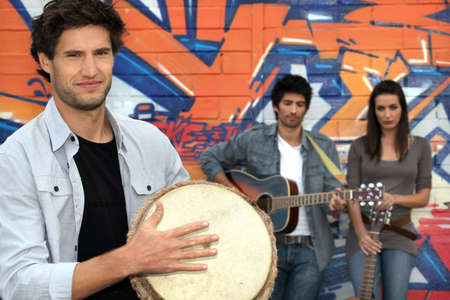 three musicians in front of a tagged wall photo