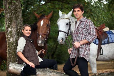 femme et cheval: Jeune couple avec deux chevaux