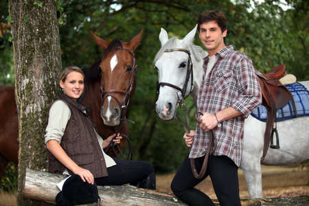 Young couple with two horses photo