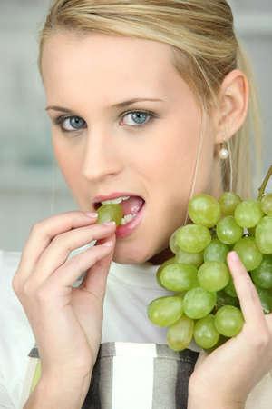 fair skinned: Woman eating white grapes