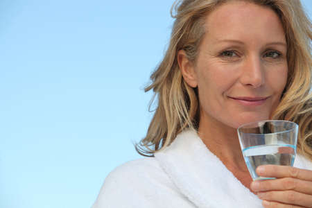Attractive blonde haired woman with no make up on and drinking a glass of water photo