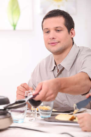 Man eating raclette photo