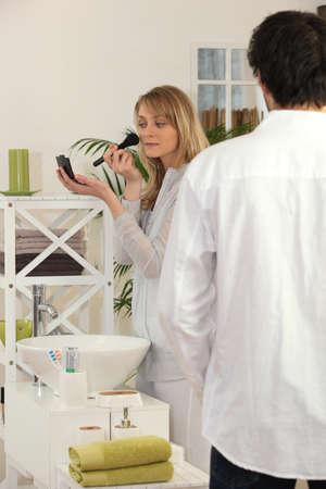 Woman applying make-up in bathroom photo
