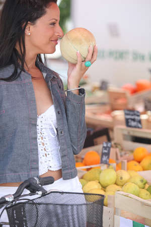 ripeness: Woman smelling a melon at market