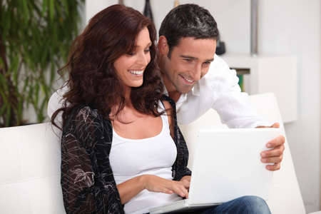 Couple looking at photos on their laptop and reminiscing photo