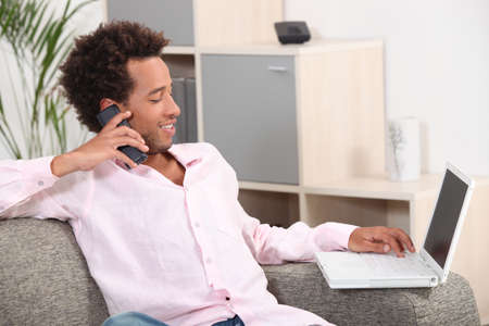 Man sat with laptop and telephone at home Stock Photo - 12500520