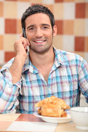 45: Man on phone at breakfast