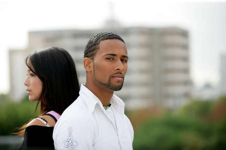 interracial love: Young couple standing back-to-back on the outskirts of a city