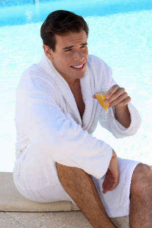 17 19 years: Man drinking orange juice by the pool Stock Photo