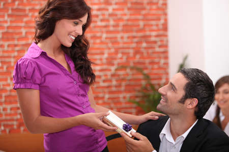 Woman offering man a small gift photo