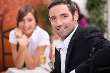 a 40 years old man and a 16 years old girl with sparkling wine on a restaurant table Stock Photo - 12499633