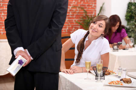 Man offering gift to woman in restaurant photo