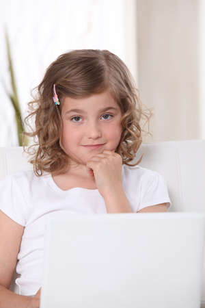 hairclip: Little girl on a sofa with laptop Stock Photo