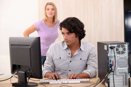 Male on his computer with his wife in the back  photo