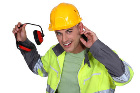 decibels: Worker holding hearing protection Stock Photo