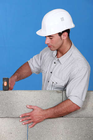 knocking: Bricklayer tapping down a block wall
