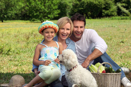 Parents and young daughter with dog and basket of vegetables photo