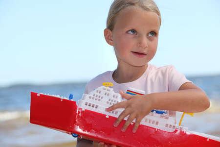 Girl holding toy ship photo