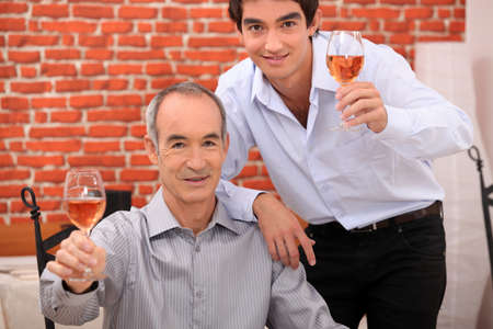 Men raising their glasses in a toast photo