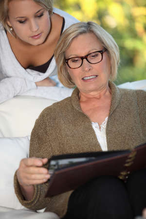 grandmother and granddaughter skimming through family album photo