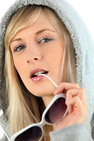 Woman in a hooded sweatshirt biting her sunglasses photo