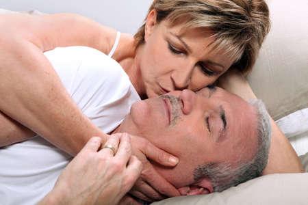 besos apasionados: Mujer besando a su marido dormido