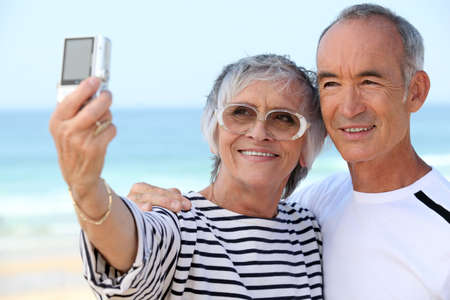 taking photograph: Older couple taking their own photograph at the beach