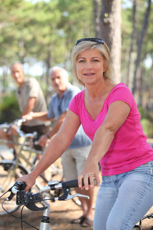 Woman riding a bike with friends in a forest photo