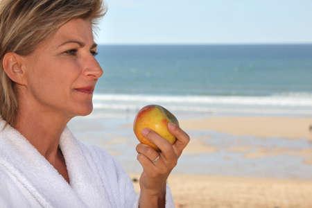 mujer mirando el horizonte: mujer rubia madura vestida con bata de comer una manzana en frente al mar