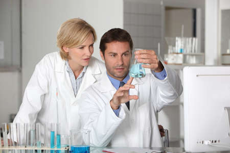 white coats: Laboratory team examining blue liquid Stock Photo