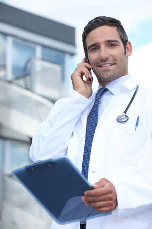 Doctor using his mobile phone outside a hospital building photo