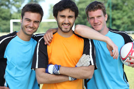 group goals: Three smiling footballers with ball Stock Photo