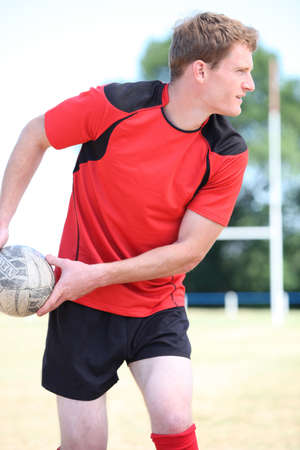 Rugby player passing ball photo