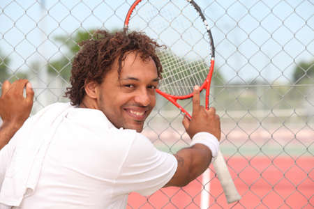 municipal court: Male tennis player leaning on the fence of a municipal hard court