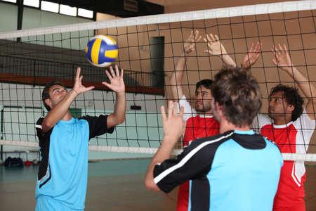 Los hombres jóvenes jugando voleibol