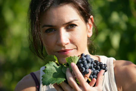 wine grower: Woman holding a bunch of grapes