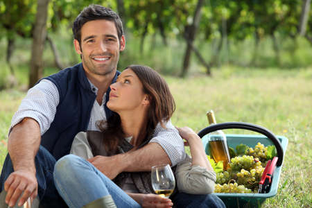 Romantic man and woman picking grapes and drinking wine photo
