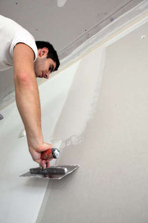 gypsum: Tradesman spreading plaster Stock Photo