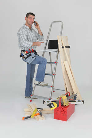 Carpenter making call to supplier photo