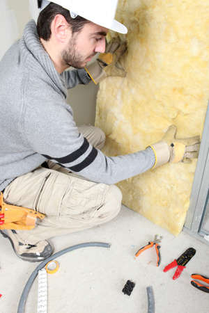 insulation: Man installing insulation Stock Photo