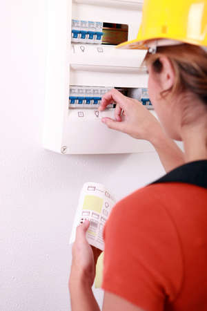 fuse box: Female electrician putting icons on a fusebox
