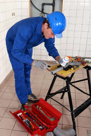 experienced plumber at work with miscellaneous tools photo