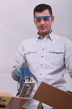 Man cutting a floorboard photo