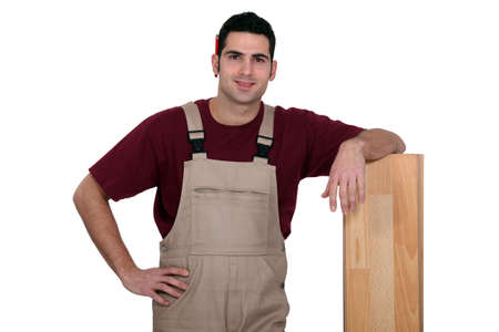 Man standing next to a wooden plank photo