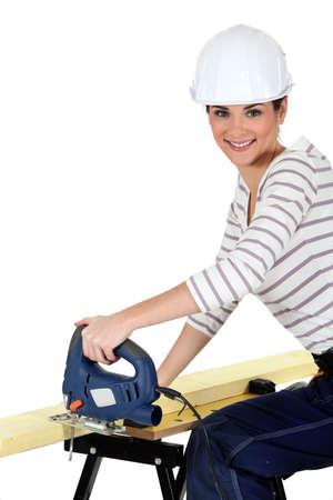 Woman cutting wood with a jigsaw photo