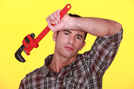 arm extended: Tired worker holding wrench Stock Photo